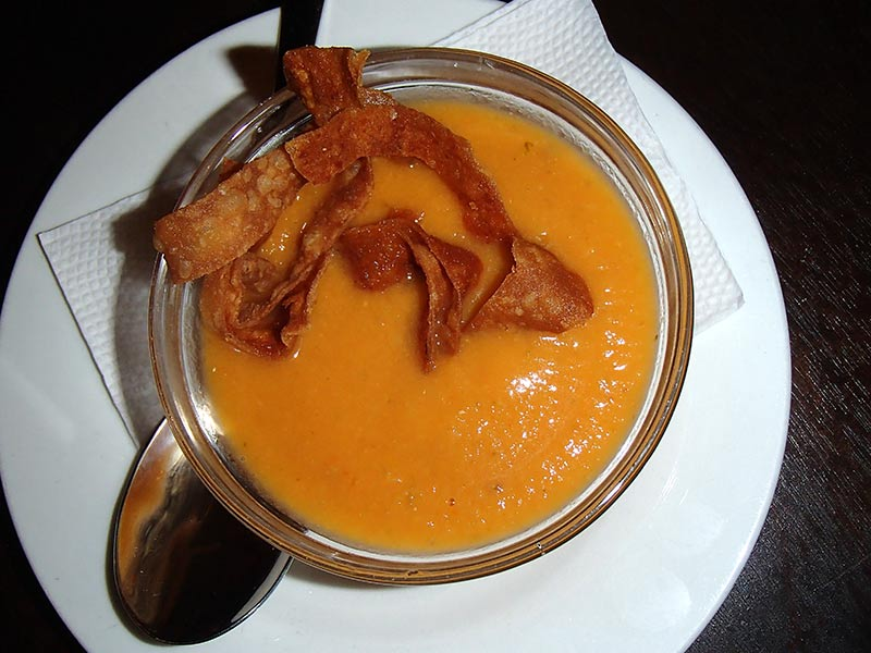 Creamy vegetable soup with fried dough garnishes.